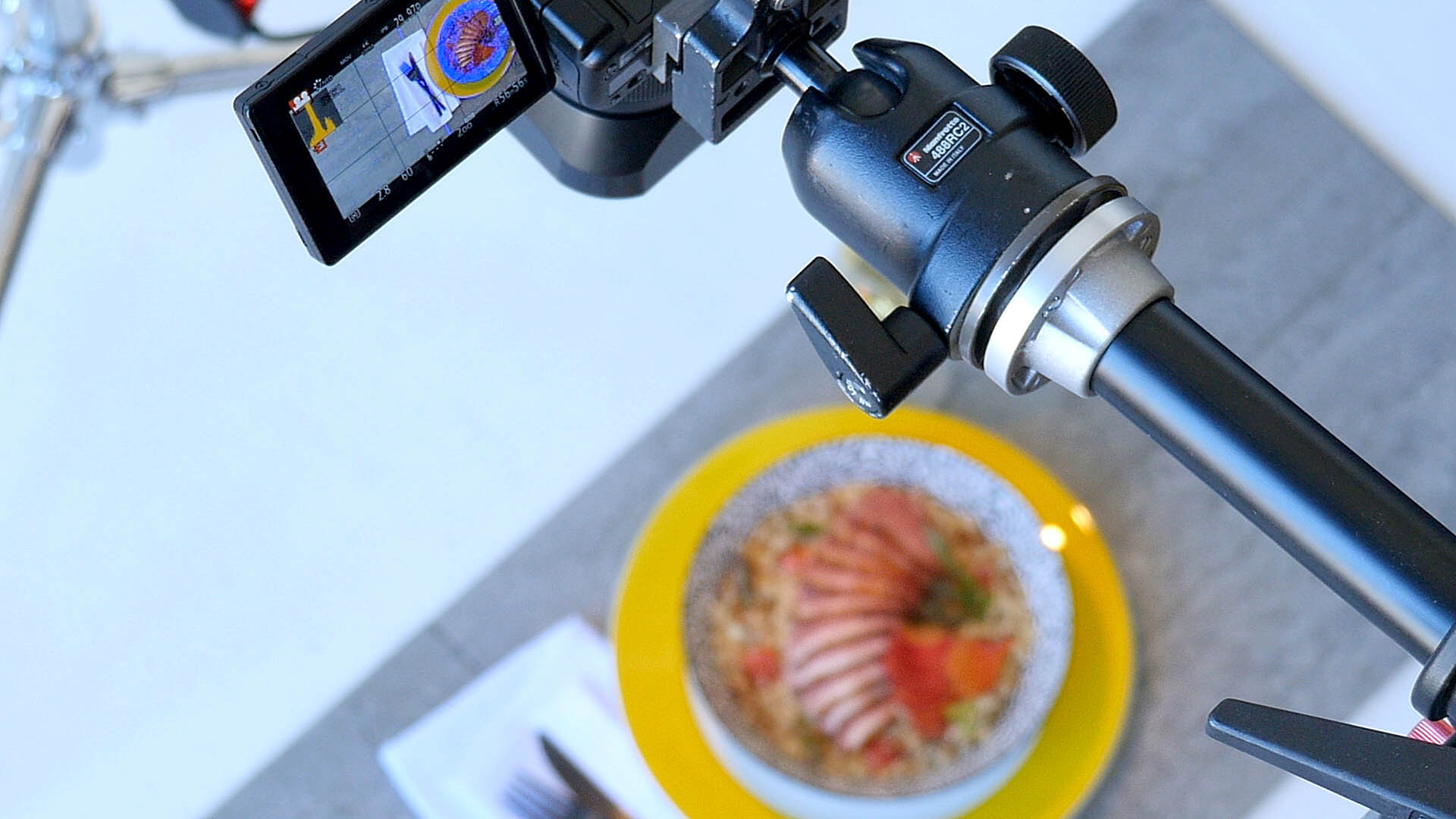 A frame grab photograph from the video Food & Camera Gear Behind the Scenes at a Food Photo Video Shoot at a Montreal Studio. The photograph shows a camera pointed down over a beautifully styled bowl of food. The bowl of food is visible in the LCD display on the camera. The camera is a Panasonic GH4 with a Panasonic 25mm f 1.4 lens. Original Food & Camera Gear Behind the Scenes at a Food Photo Video Shoot at a Montreal Studio video posted here https://www.youtube.com/watch?v=Fz8r8y5M-uc