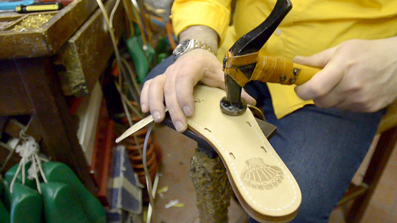 sandal maker Shoe Maker in Sorrento Italy hammering a strap to the soul of a pair of  Custom